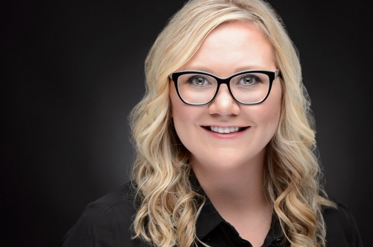 blond woman with glasses smiling for linked headshot